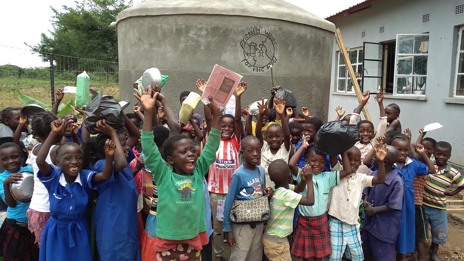 Monze children around water catchment